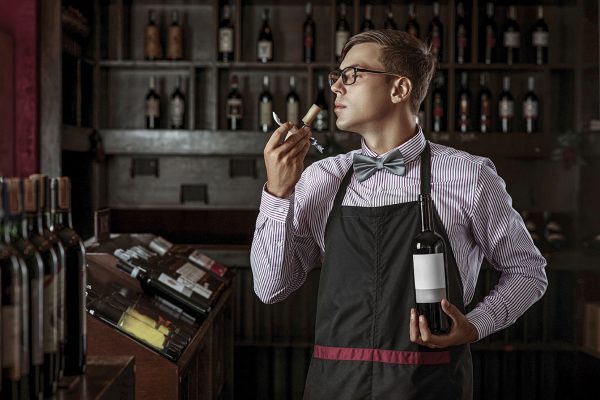 A professional sommelier demonstrates his skills by smelling a cork from a freshly opened wine drink. Sommelier.